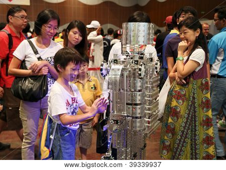 SUBANG JAYA - NOVEMBER 10: Unidentified visitors interact with a robot at the World Robot Olympaid on November 10, 2012 in Subang Jaya, Malaysia. This year's theme is Robots connecting people.