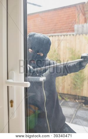 Buglar opening door from outside with crow bar