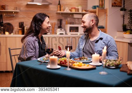 Husband Proposing Wife To Marry Him In Kitchen During Romantic Dinner. Man Making Proposal To His Gi