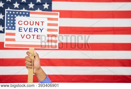 Hands Holding Count Every Vote Sign Board With Us Flag As Background With Copy Space - Concept Of Vo