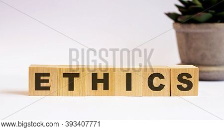The Word Ethics On Wooden Cubes On A Light Background Near A Flower In A Pot. Defocus