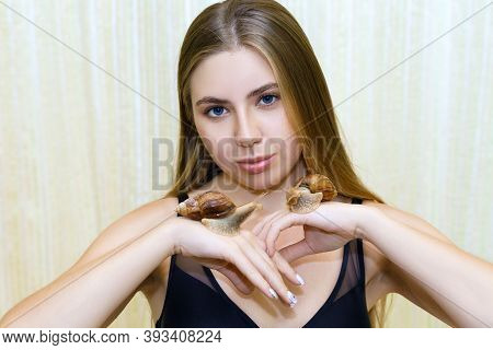 Young Woman With Clean Healthy Skin Holds Large Snails In Her Palms After Cleansing And Rejuvenating