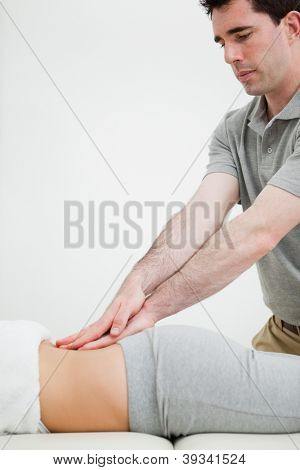 Close-up of a masseur massaging the back of a woman in a room
