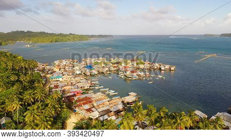 Traditional Fishing Village In Asia With Fishing Boats And Houses Standing In The Sea. Philippines,