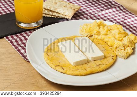 Tasty Traditional Breakfast In Colombia; Arepa Of Yellow Corn With Cheese And Scrambled Eggs.