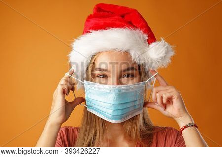 Cheerful Young Blonde Woman Wearing Santa Hat.and Face Mask