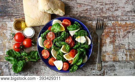 Caprese Salad In A Blue Plate. Healthy Salad With Tomatoes, Basil And Mozzarella.