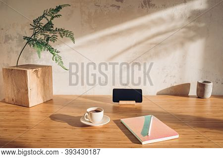 Bloggers Workplace Without Anything Superfluous. Desk With Cell Phone, Notebook And Cup Of Coffee In