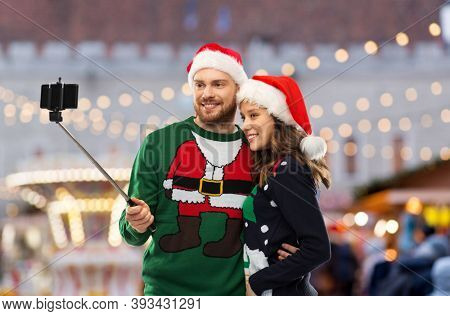 people, technology and holidays concept - happy couple in santa hats and ugly sweaters taking picture by smartphone on selfie stick over christmas market background
