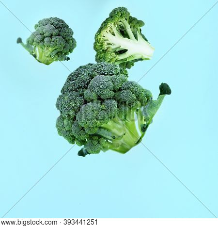 Flying Green Broccoli Slices On A Blue Background. Concept Of Flying Food, Green Vegetables, Diet Fo