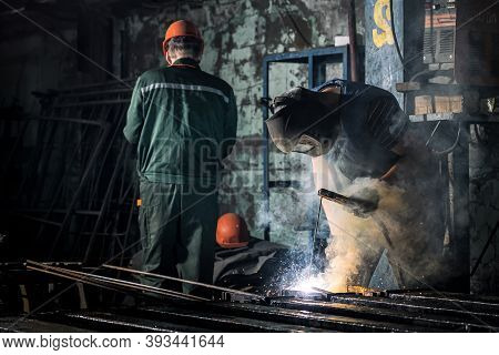 Industrial Worker At A Factory Welding Steel Structure. A Worker With A Protective Mask Is Welding M