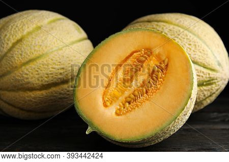 Tasty Fresh Melons On Black Wooden Table, Closeup