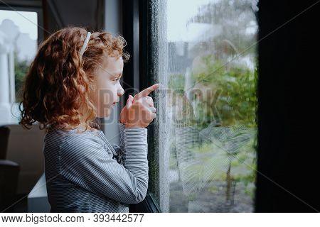 Cute Little Girl Standing Near Window Looking At Rain Outside