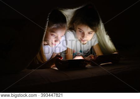 Two Sisters Play Games On Their Smartphones At Night Under The Covers. One Girl Looks Into Her Siste