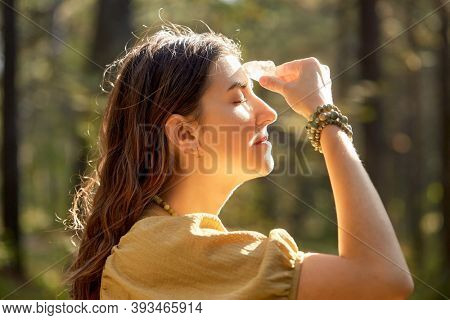 occult science and supernatural concept - young woman or witch with semiprecious crystal or gemstone performing magic ritual in forest