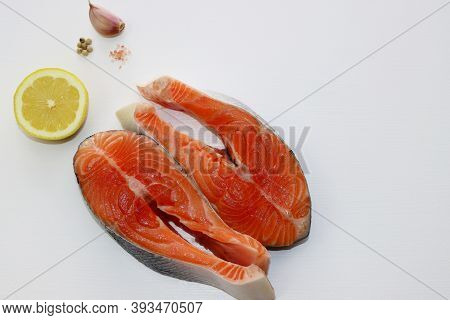 Two Large And Fatty Salmon Steaks On A White Background. Salmon, Salt, Pepper And Lemon.