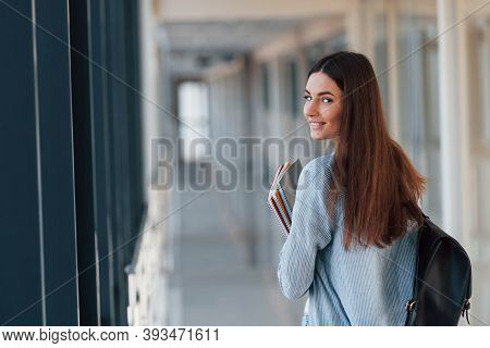 Rear View Of Female Young Student That Is In Corridor Of A College And Holding Notepads.