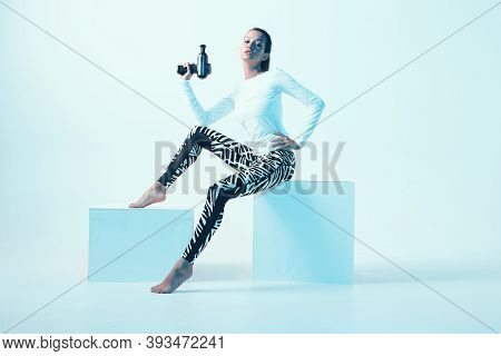 Percussion Massager, Athletic Young Fit Female Showing Handheld Massaging Gun Sitting On Cube In Neo