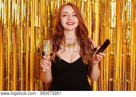 Beautiful Caucasian Woman Smile With Cellphone In Hands And Drinking White Wine, Looking At Camera W