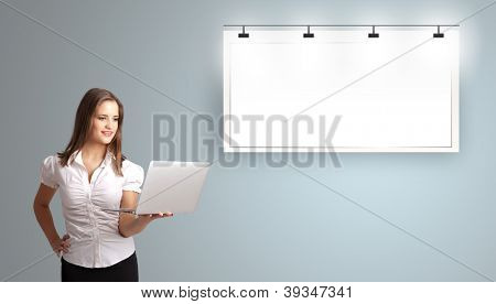 beautiful young woman holding a laptop  and presenting modern copy space