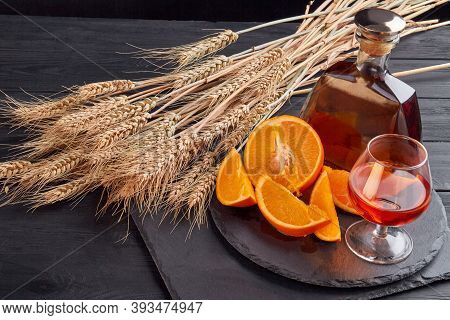 Wheat Ears With Orange Piece And Alcohol. Still Life Composition Glass Of Whiskey And Bottle.