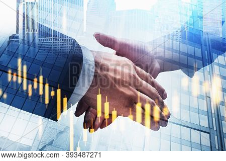 Businessman And Businesswoman Shaking Hands In Blurry City With Double Exposure Of Financial Chart.