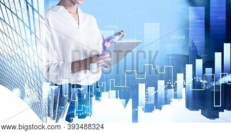Unrecognizable Businesswoman Using Tablet In Blurry City With Double Exposure Of Financial Graph. To