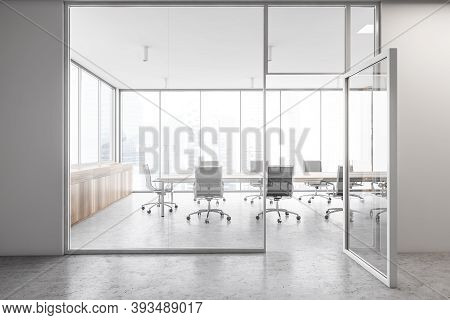 Wooden White Office Meeting Room With Glass Door Opened, Long Wooden Table With Black Chairs Inside.