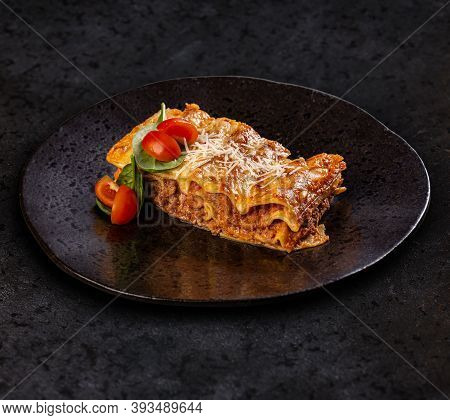 Tasty Lasagne With Meat Covered With Cheese Served On Black Plate