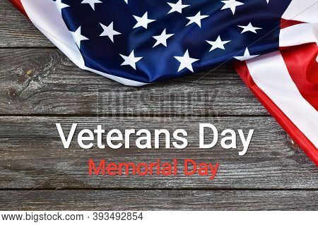 Veterans Day. Text Written Veterans Day, Memorial Day On A Wooden Background And Flag Of The United
