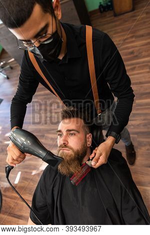 A Bearded Boy Has His Beard Combed By A Barber With A Comb And A Hairdryer, And Mask For Pandemic Pr