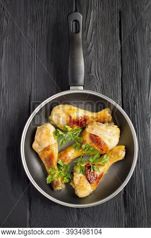 Top View Of Fried Chicken Legs In The Frying Pan On The Black Wooden Background. Location Vertical.