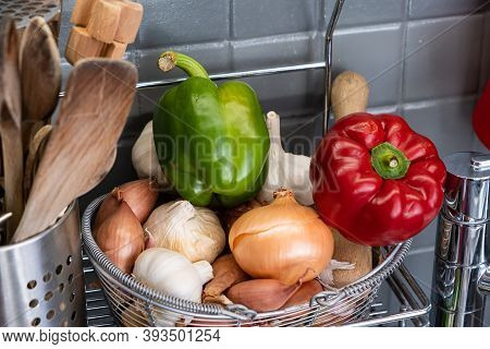 Small Basket In The Kitchen Next To The Utensils With Garlic, Onions, Shallots And Red Yellow And Gr