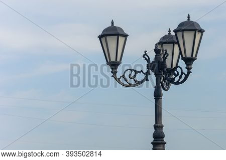 Retro Street Lamp Against The Blue Sky. An Old-fashioned Wrought Iron Lamppost With Beautiful Decora