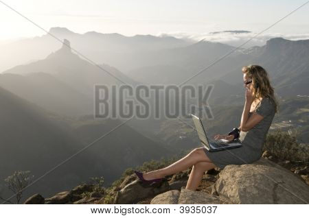 Woman Working With Portable Laptop In The Mountain