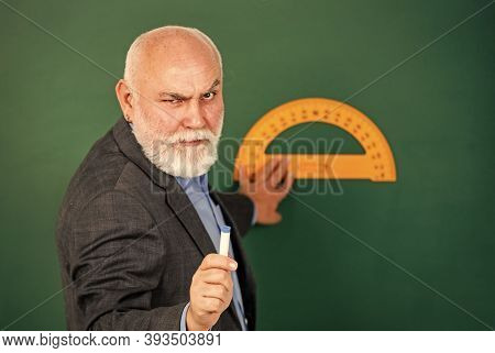 Serious And Strict. Home Learning. Senior Man Teacher Use Protractor Tool. Bearded Tutor Man Draw Wi