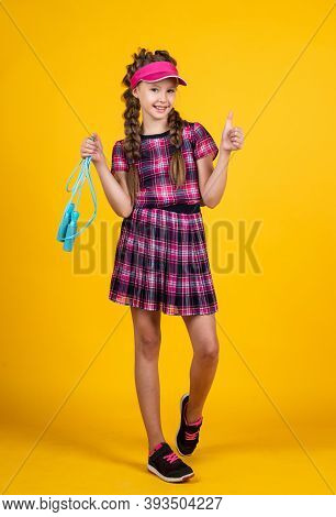 Sport Is Our Life. Happy Girl Holding Sport Equipment. Kid Hold Tennis Racket. Child Wear Ftness Cap
