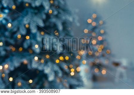 Defocused Christmas Tree With Lights And Ornaments. Blurred Silhouette Of A Christmas Tree With Ligh