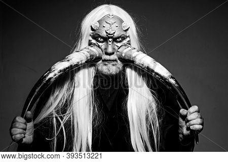 Elderly Man Holding Two Red Horns. Demon Head Isolated On Black. Ancient Alchemy. Devil Horns. Beard