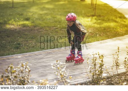 Active Sport. A Cute Girl Is Rollerblading In The City Park.