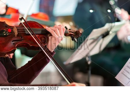 Symphony Music. Male Musician Playing The Violin In Orchestra. Focus On Bow