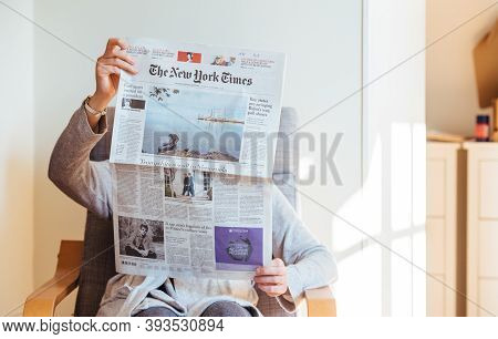 Paris, France - Nov 5, 2020: Woman Reading In Living Room The Latest The New York Times Newspaper Fe