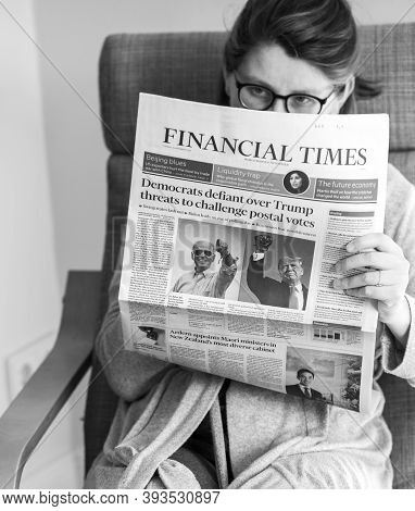 Paris, France - Nov 5, 2020: Black And White Image Woman Reading Financial Times In Living Room The