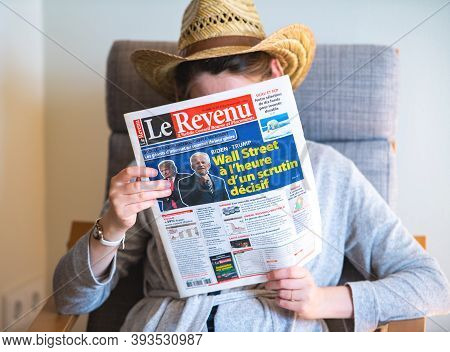 Paris, France - Nov 5, 2020: Woman Reading In Living Room The Latest Le Revenu Newspaper Featuring O
