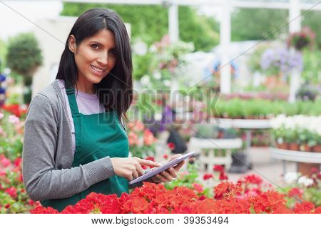 Smiling employee using tablet pc to check red flowers in garden center