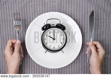 Hands Holding Knife And Fork Above Alarm Clock On White Plate On Tablecloth Background. Intermittent