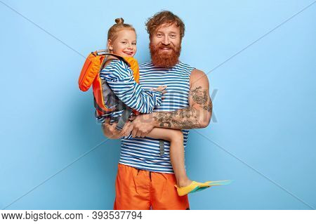Happy Affectionate Father Carries Small Daughter On Hands Who Wears Protective Lifejacket And Flippe