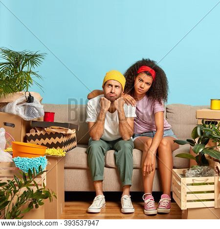 Photo Of Multiethnic Couple Pose On Sofa, Have Tired Face Expressions, Dressed Casually, Busy During