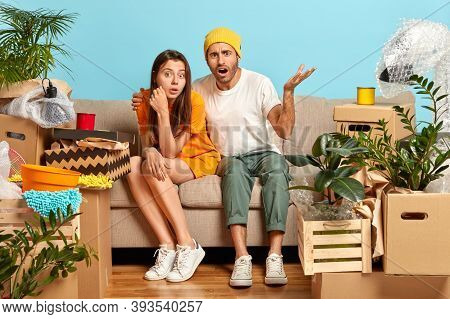 Woman And Man Tenants Pose At Cozy Sofa In Empty Messy Room With Different Household Things, Frustra