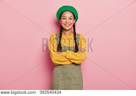 Candid Shot Of Happy Chinese Millennial Girl Keeps Arms Folded, Smiles Pleasantly At Camera, Enjoys